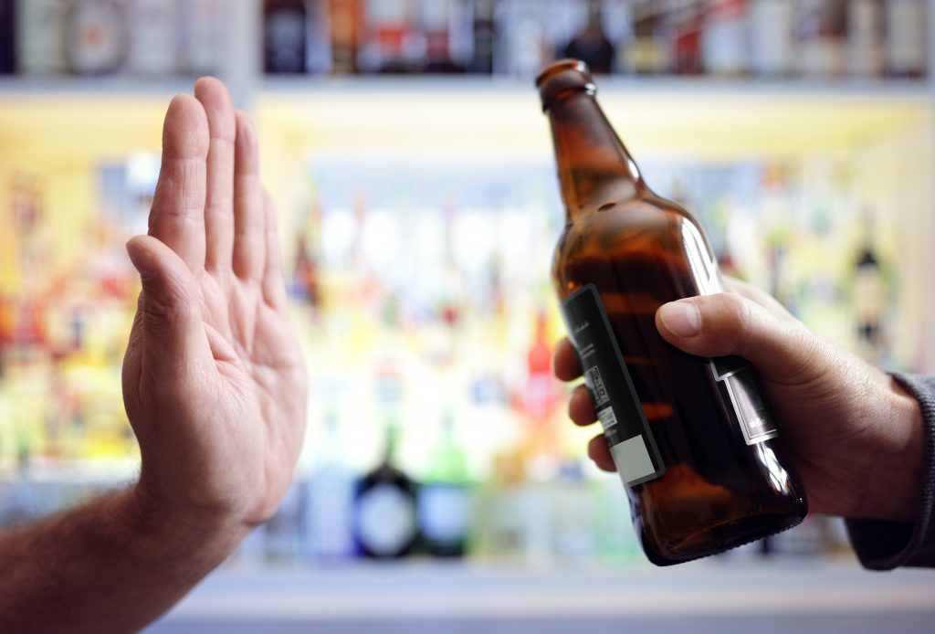 hand rejecting a bottle of beer and quitting alcohol