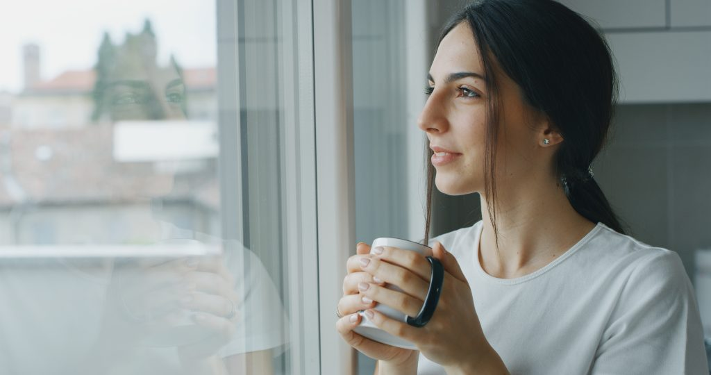 Woman holding a mug of coffee looking out the window smiling