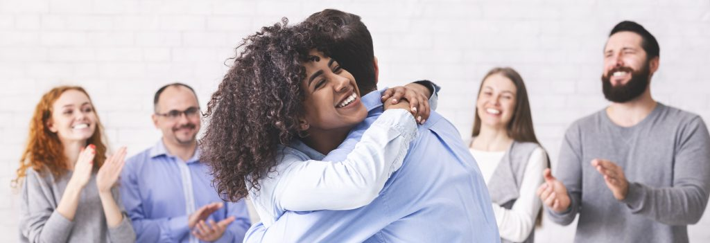 Woman hugging a man in a support group