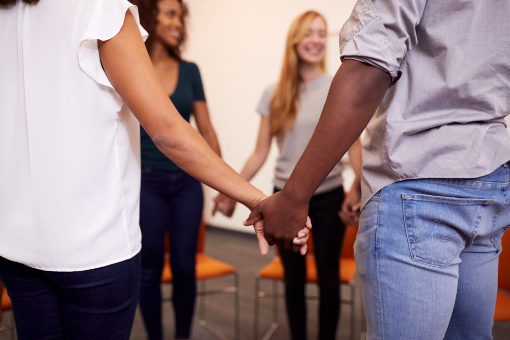 Group therapy standing in a circle holding hands