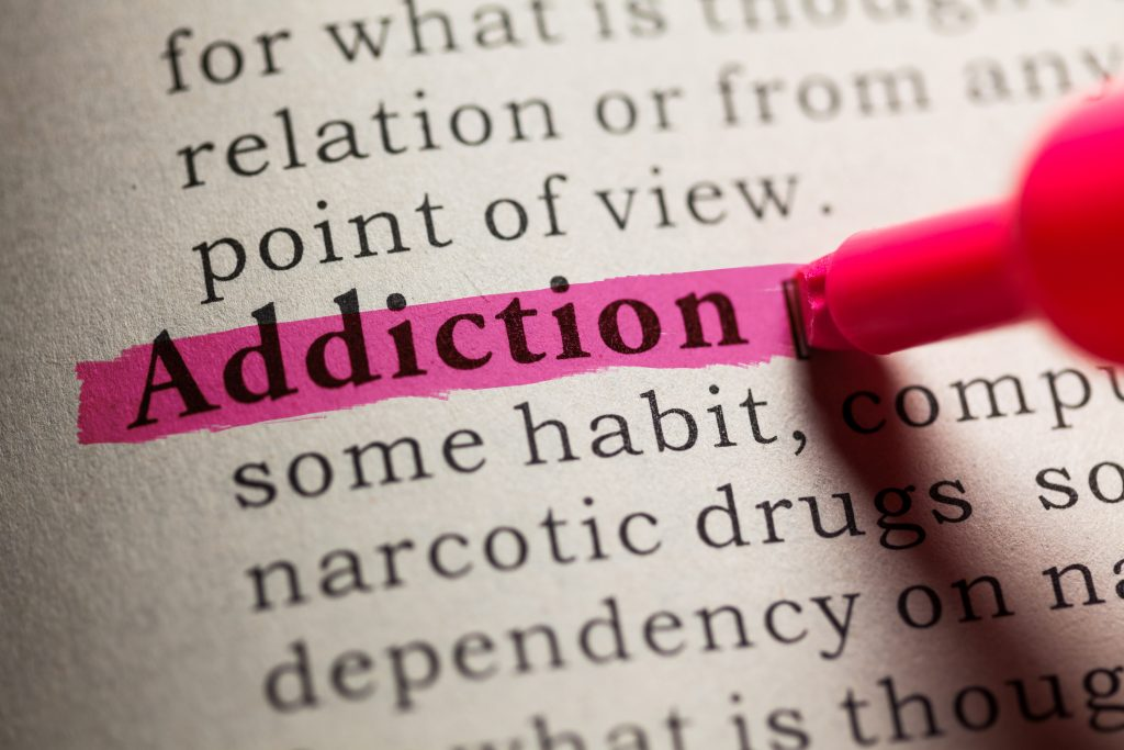 Addiction dictionary definition highlighted in pink