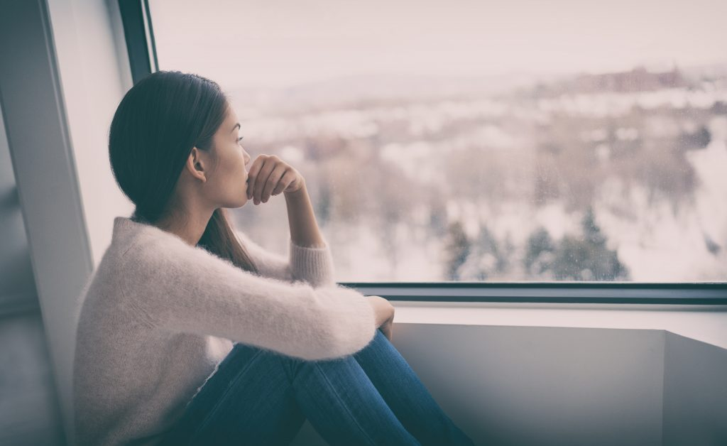 woman looking out of a window with depression