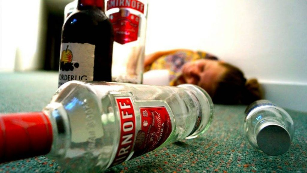 alcoholic on the ground with a bottle of vodka