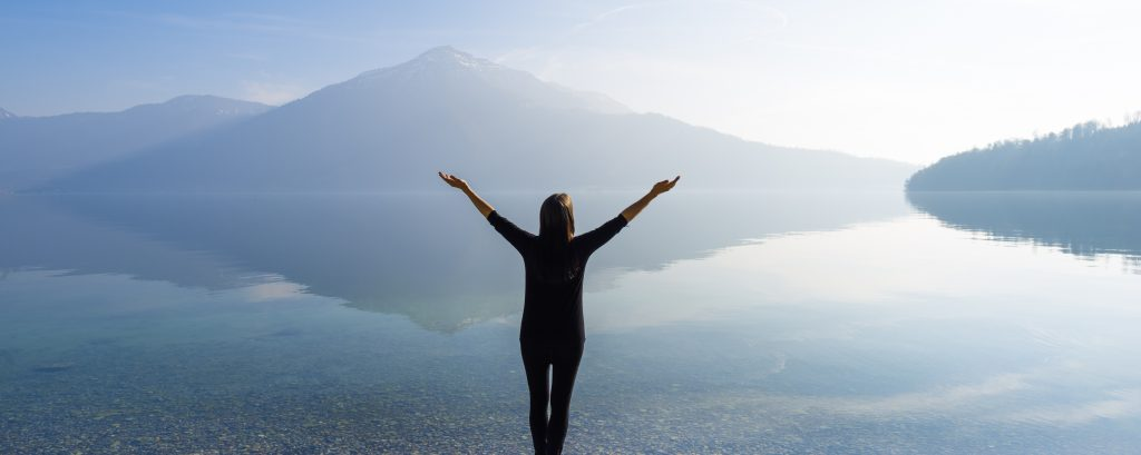 Woman with open arms by the lake on a background of mountains.