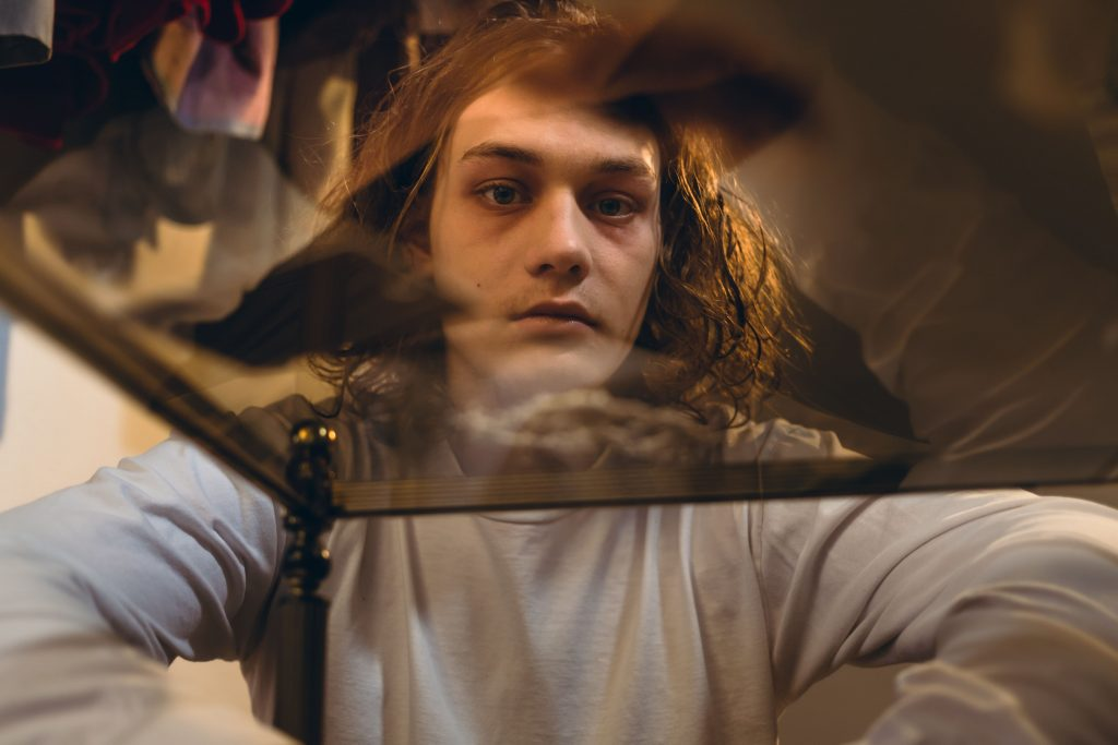boy looking through a glass table at some drugs